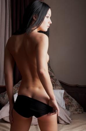 intymno: Młoda kobieta brunette nagie stałego w jej Sypialnia