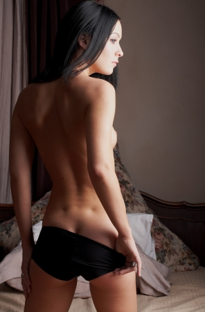 sexual intimacy: Young nude brunette woman standing in her bedroom