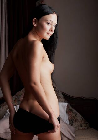female sexuality: Young nude brunette woman standing in her bedroom