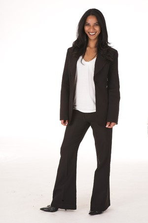 Young adult African-Indian businesswoman in casual office outfit with black pants and high heels with a dark jacket on a white background. Not Isolated photo