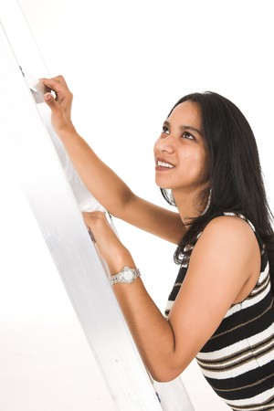 Young adult African-Indian businesswoman in casual office outfit Metaphorically climbing the ladder of success. Shot on a white backgroun, Not Isolated photo