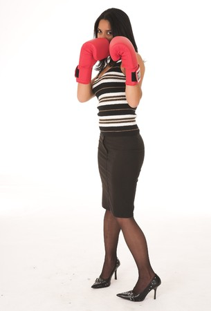 Young adult African-Indian businesswoman in red boxing gloves as a metaphor for office politics on a white background. Not Isolated photo