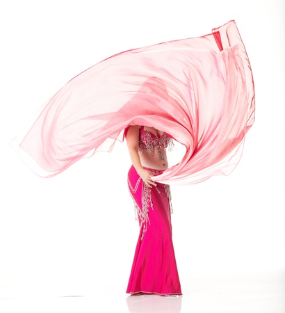 exotic dancer: Lithe adult caucasian belly dancer with red hair and pink belly dancing outfit performing a dance with veils on a white background. Not Isolated Stock Photo