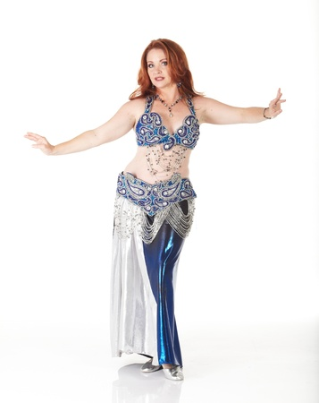 belly dancing: Lithe adult caucasian belly dancer with red hair and a blue belly dancing outfit performing steps on a white background. Not Isolated Stock Photo