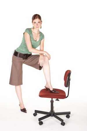 short sleeved: A tall smiling Caucasian businesswoman with brown trousers, a short sleeved green top and gold jewelry. Not Isolated Stock Photo