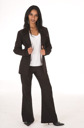 Young adult African-Indian businesswoman in casual office outfit with black pants and high heels with a dark jacket on a white background. Not Isolated