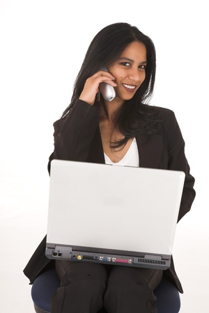 typist: Young adult African-Indian businesswoman in casual office outfit sitting with a notebook computer on her lap on a typist chair on a white background. Not Isolated
