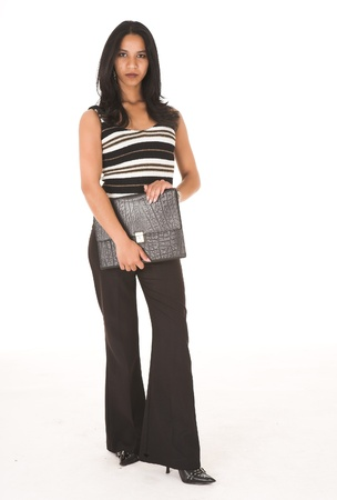 Young adult African-Indian businesswoman in casual office outfit with black pants, a striped top and high heels on a white background, carrying a leather folder. Not Isolated photo