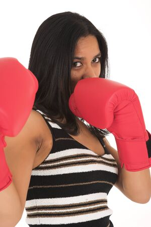 office politics: Young adult African-Indian businesswoman in red boxing gloves as a metaphor for office politics on a white background. Not Isolated