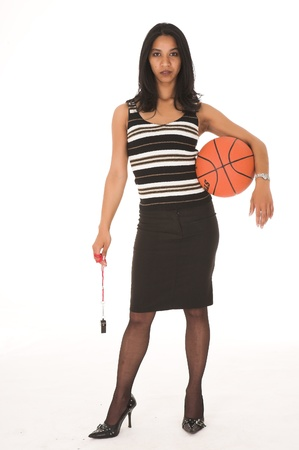 Young adult African-Indian businesswoman in casual office outfit with a black pencil skirt, a striped brown top and high heels on a white background as a coach, trainer or team owner. Not Isolated photo