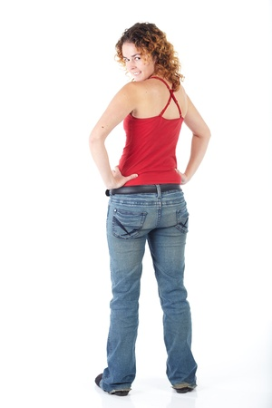 Cute young adult caucasian woman wearing a red top and jeans and with curly red hair on a white background. Not Isolated photo