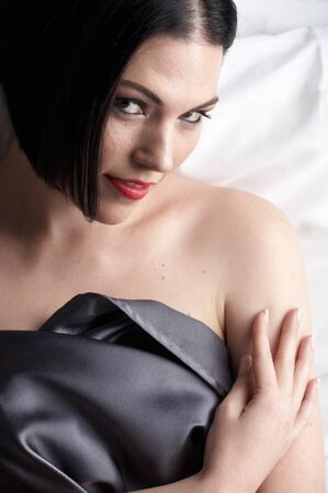 Sexy naked young caucasian adult woman with red lips, short black hair and a pierced eyebrow, covered in a dark satin sheet and sitting on a bed photo