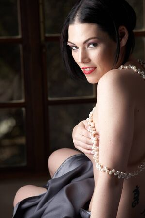 Sexy naked young caucasian adult woman with red lips, short black hair and a pierced eyebrow, covered in a dark satin sheet and sitting on a bed and wearing a string of pearls photo