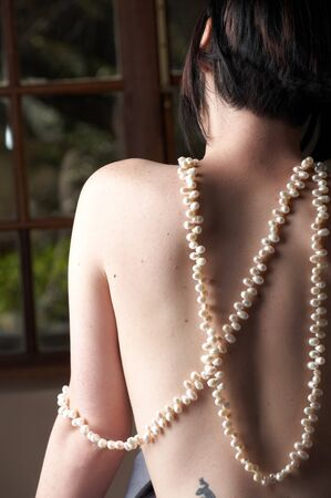Sexy naked young caucasian adult woman with short black hair and covered in a dark satin sheet, sitting on a bed with her back to the camera and wearing a string of pearls Stock Photo - 8239649