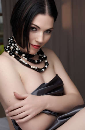 Sexy naked young caucasian adult woman with red lips, short black hair and a pierced eyebrow, covered in a dark satin sheet and wearing a black and white pearl string necklace photo