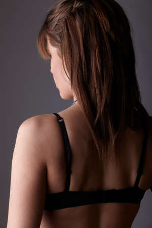 Young adult caucasian woman wearing black lace lingerie from behind, on a neutral grey background. photo