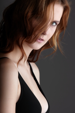 fair skin: Mujer joven pelirroja adultos cauc�sicos con ojos verdes y piel muy blanca en lencer�a negra sobre un fondo gris neutro