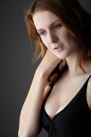 fair skin: Mujer joven pelirroja de adultos del C�ucaso con ojos verdes y una piel muy blanca en un vestidito negro sobre un fondo gris neutro