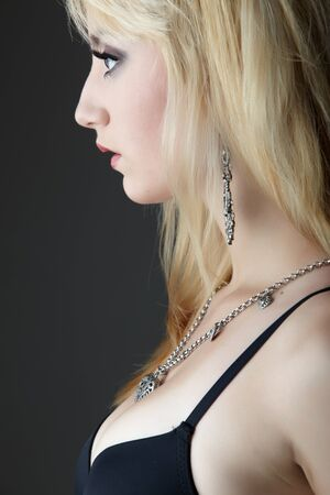 Young adult caucasian woman with blonde hair and prominent jewelry on a neutral grey background with black lingerie and big brown eyes Stock Photo - 8729035