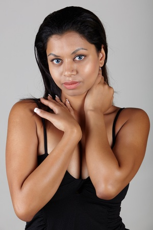 fuller figure: Young voluptuous Indian adult woman with long black hair wearing black lingerie and blue coloured contact lenses on a neutral grey background. Mixed ethnicity