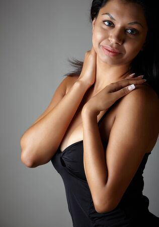 Young voluptuous Indian adult woman with long black hair wearing a black dress and blue coloured contact lenses on a neutral grey background. Mixed ethnicity photo