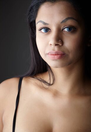 Young voluptuous Indian adult woman with long black hair wearing black lingerie and blue coloured contact lenses on a neutral grey background. Mixed ethnicity Stock Photo - 8728801