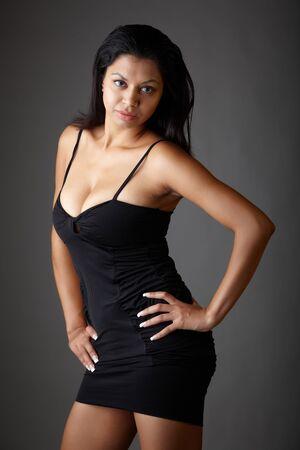 voluptuous: Giovane voluttuosa adulta donna indiana con lunghi capelli neri che indossa un abito nero e lenti a contatto colorate blu su sfondo grigio neutro. Etnia mista