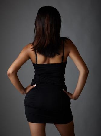 lentes contacto: Voluptuosa India adulta joven con pelo largo y negro que llevaba un vestido negro y lentes de contacto de colores azules sobre un fondo gris neutro. Origen �tnico mixto Foto de archivo