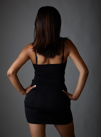 curvy: Young voluptuous Indian adult woman with long black hair wearing a black dress and blue coloured contact lenses on a neutral grey background. Mixed ethnicity