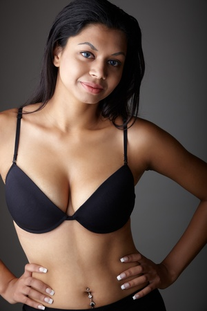 undressed young: Young voluptuous Indian adult woman with long black hair wearing black lingerie and blue coloured contact lenses on a neutral grey background. Mixed ethnicity
