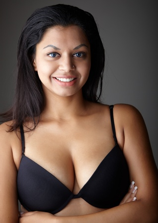 Young voluptuous Indian adult woman with long black hair wearing black lingerie and blue coloured contact lenses on a neutral grey background. Mixed ethnicity Stock Photo - 8729054