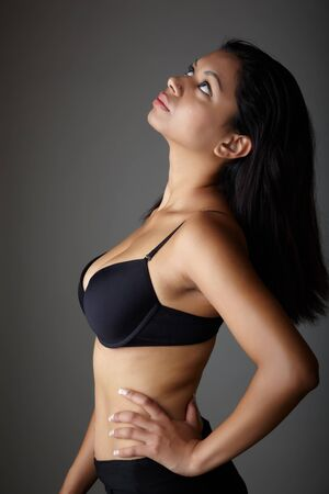 Young voluptuous Indian adult woman with long black hair wearing black lingerie and blue coloured contact lenses on a neutral grey background. Mixed ethnicity Stock Photo - 8729037