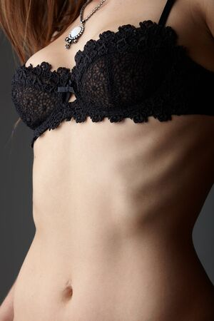 Young adult caucasian woman wearing black lace lingerie on a neutral grey background. Stock Photo - 9048892