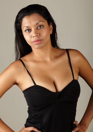 Young voluptuous Indian adult woman with long black hair wearing a black dress and blue coloured contact lenses on a neutral grey background. Mixed ethnicity Stock Photo - 9048845