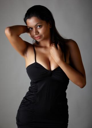 voluptuous: Giovane voluttuosa adulta donna indiana con lunghi capelli neri indossa un abito nero e blue lenti a contatto colorate su uno sfondo grigio neutro. Etnia mista