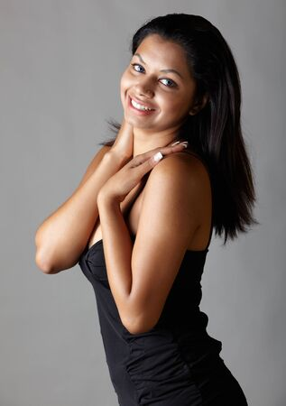 Young voluptuous Indian adult woman with long black hair wearing a black dress and blue coloured contact lenses on a neutral grey background. Mixed ethnicity Stock Photo - 9048843