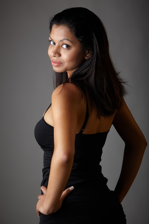 Young voluptuous Indian adult woman with long black hair wearing a black dress and blue coloured contact lenses on a neutral grey background. Mixed ethnicity Stock Photo - 9048847
