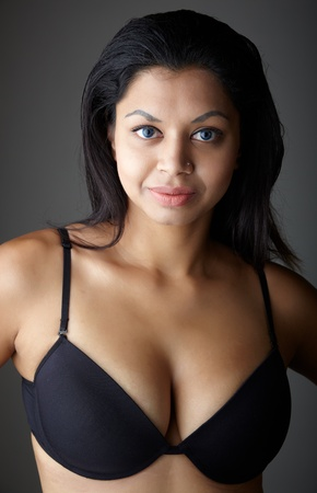 big boobs: Voluptuosa India adulta joven con pelo largo y negro vistiendo ropa interior negro y lentes de contacto de colores azules sobre un fondo gris neutro. Origen �tnico mixto