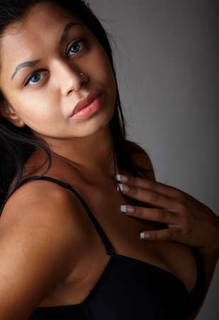 Young voluptuous Indian adult woman with long black hair wearing black lingerie and blue coloured contact lenses on a neutral grey background. Mixed ethnicity Stock Photo - 9048838
