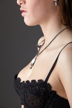 Young adult caucasian woman wearing black lace lingerie on a neutral grey background. Stock Photo - 10070031