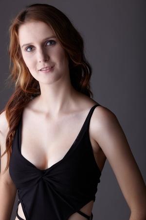 fair skin: Mujer joven pelirroja adultos cauc�sicos con ojos verdes y piel muy blanca en un peque�o vestido negro sobre un fondo gris neutro
