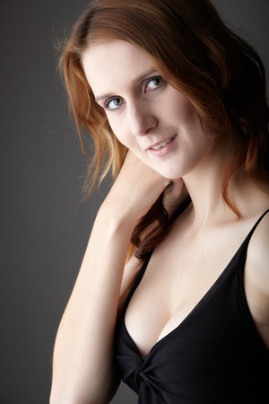lbd: Young caucasian adult redhead woman with green eyes and very fair skin in a little black dress on a neutral grey background