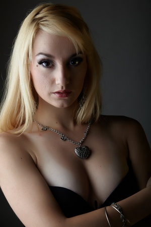 sexy nude blonde: Young adult caucasian woman with blonde hair and prominent jewelry on a neutral grey background with black lingerie and big brown eyes