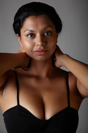 voluptuosa: Voluptuosa India adulta joven con pelo largo y negro, luciendo un vestido negro y lentes de contacto colores azules sobre un fondo gris neutro. Origen étnico mixto