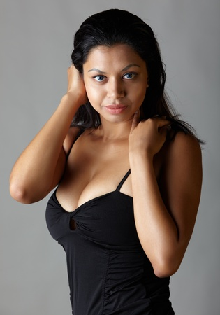 fuller figure: Young voluptuous Indian adult woman with long black hair wearing a black dress and blue coloured contact lenses on a neutral grey background. Mixed ethnicity