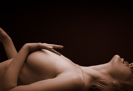Artistic Sepia tone image of a nude adult woman lying on her back against a dark background with a hand softly stroking her left naked breast. Copy Space