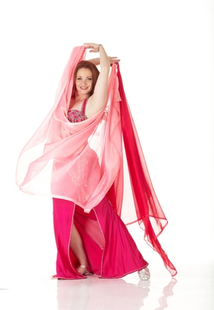 belly dance: Lithe adult caucasian belly dancer with red hair and pink belly dancing outfit performing a dance with veils on a white background. Not Isolated Stock Photo