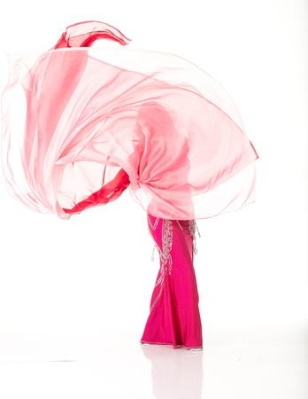 buikdansen: Lenige volwassen blanke buikdanseres met rood haar en roze buikdansen outfit het uitvoeren van een dans met sluiers op een witte achtergrond. Niet geïsoleerd Stockfoto
