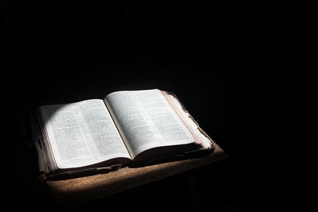 Old open bible lying on a wooden table in a beam of sunlight (not an isolated image) Shallow Depth of field – Focus on middle text