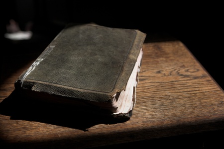 "Leather covered old bible lying on a wooden table in a beam of sunlight Shallow Depth of field – Focus on Text ""Holy Bible"" Stock Photo"